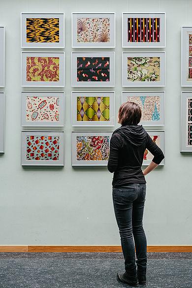 Studentin vor einer Wand mit historischen Stoffmustern