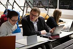 Eine Studentin und Oliver Rump arbeiten am Laptop