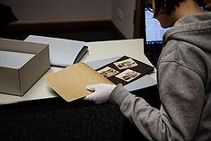 Studentin blättert mit der linken behandschuten Hand in einem alten Buch, mit der rechten Hand bedient sie eine Laptoptastatur